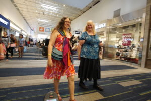 Veronica carrying Hestia in her rainbow pouch, walking with Cyndy
