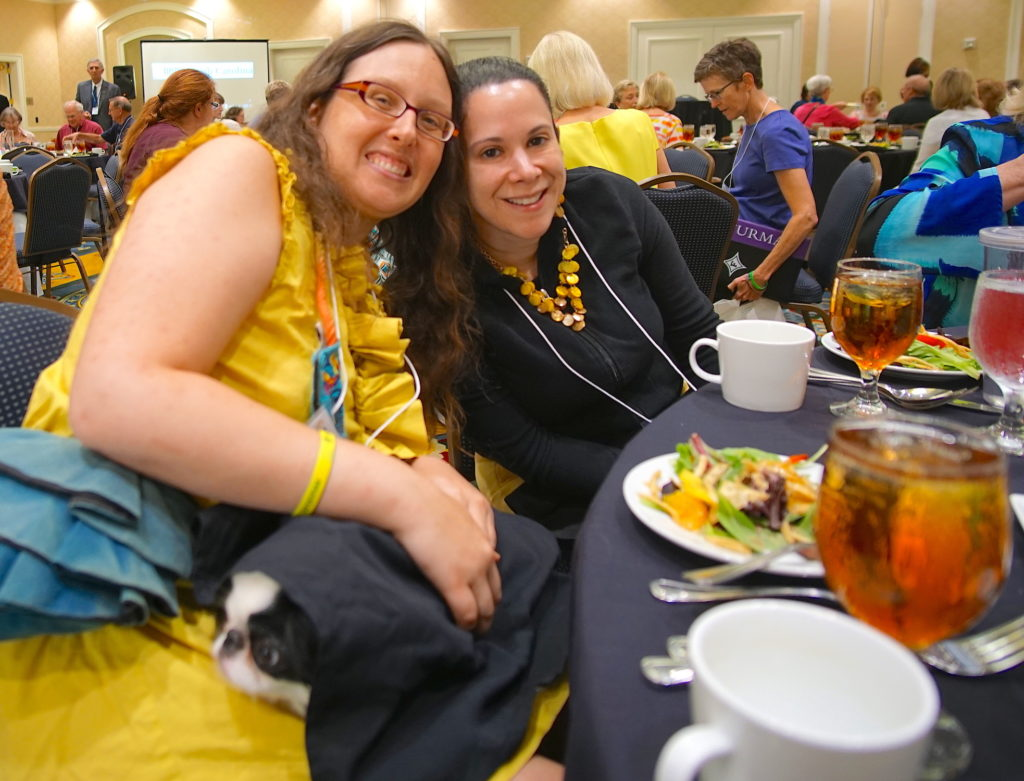 Veronica and Laura at lunch in matching yellow outfits, and Hestia underneath a napkin.