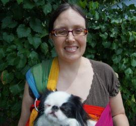 Veronica with Hestia in a rainbow sling. Hestia looks like she is sleeping