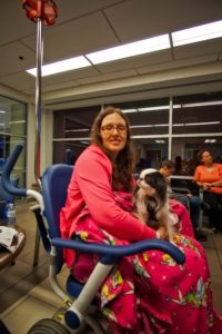 Veronica attempts to smile with Hestia on her lap in the ER in a wheelchair