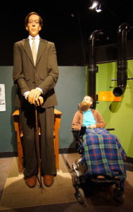 Brad fully elevated in his wheelchair next to an animatronic of the tallest man ever