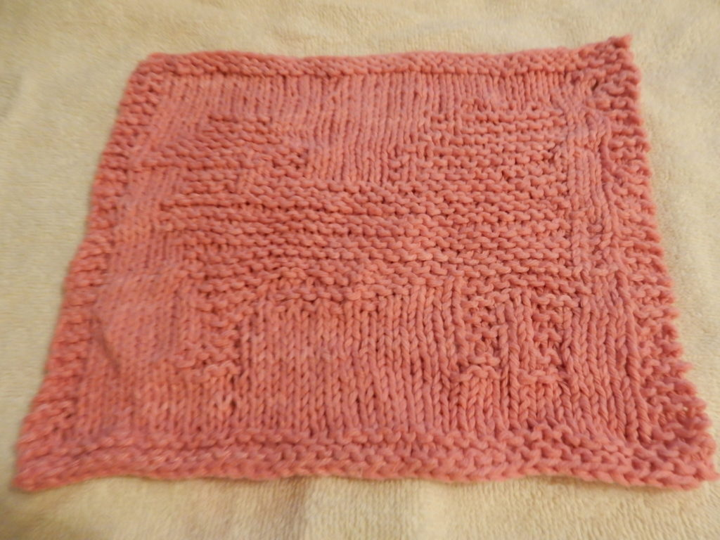 Pink knitted washcloth with Japanese Chin on it