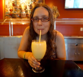 Veronica slurping up a Mango Lassi through a straw