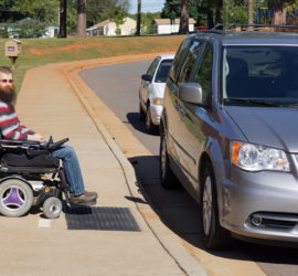 Brad in hs wheelchair at the start of a curb cut which is being totally blocked by a van.