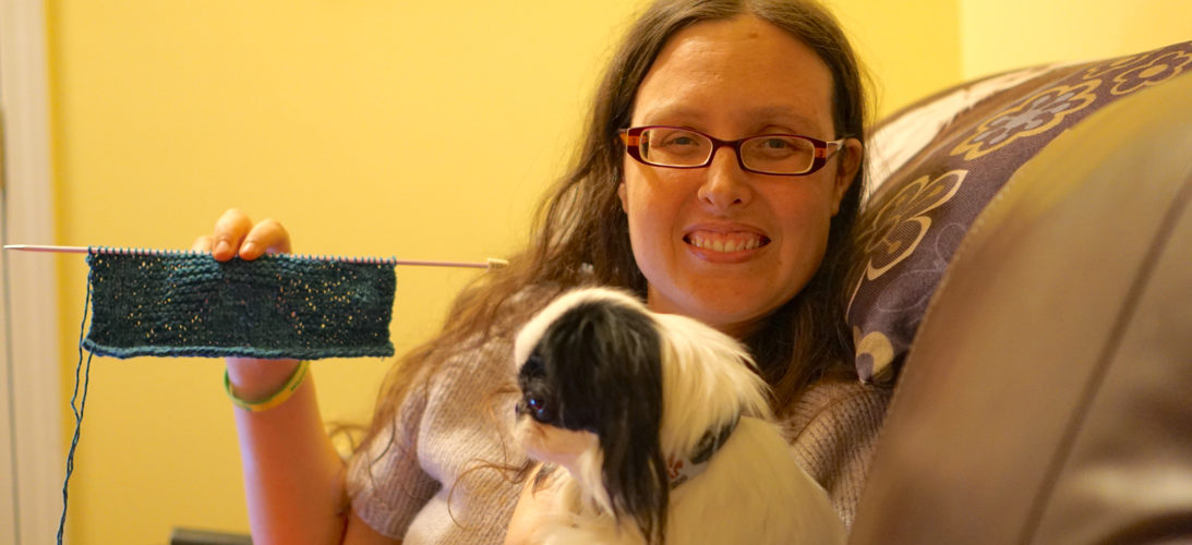 Veronica holding up her knitting (blue Japanese Chin washcloth), holding Hestia in her other arm, and smiling