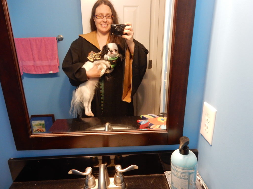 Selfie of me in my Hufflepuff cape and Hestia in her Hufflepuff vest.