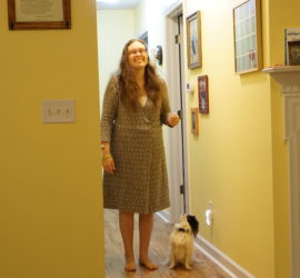 Veronica in her new wool dress laughing, while Hestia sits in heel looking up at her.