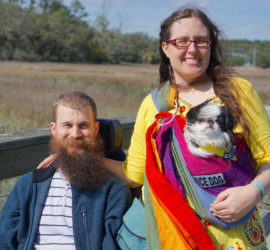 Brad and Veronica on a boardwalk overlooking a marsh. Brad's beard and Veronica and Hestia's hair are windblown to the right. Hestia is in her rainbow pouch, and Veronica has a bright yellow shirt on.