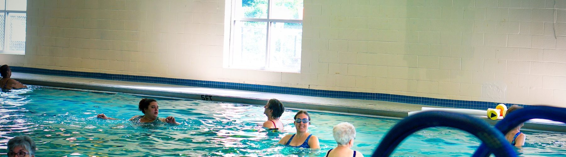 Veronica in the middle of the pool wearing a blue swimsuit and blue goggles with her hair in a bun. There are several older ladies clustered around working out, too.
