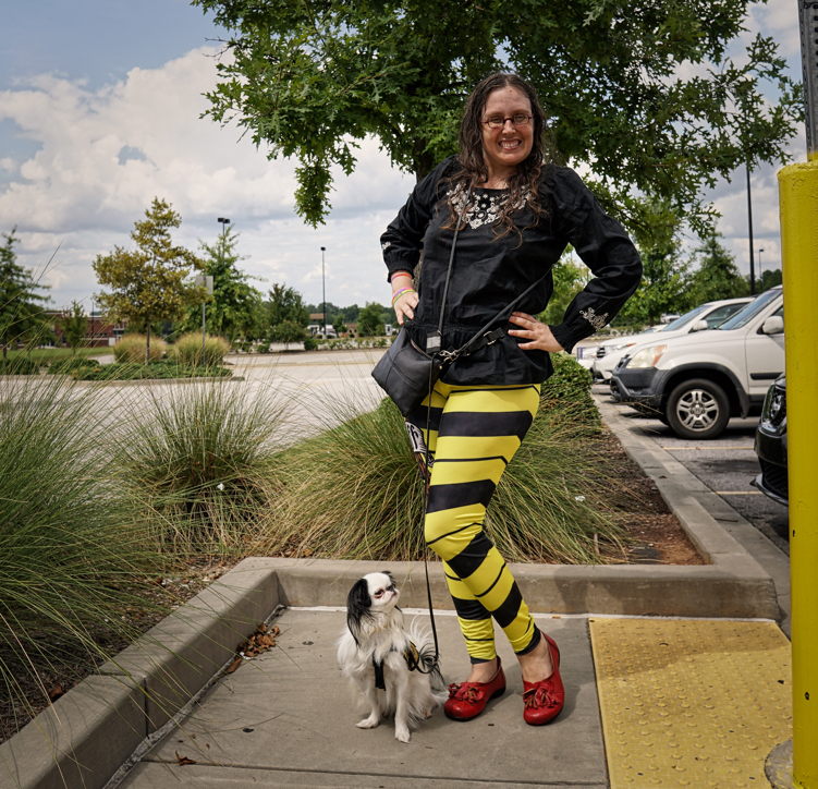 Veronica wearing black and yellow striped leggings and a black long sleeved shirt,and red shoes.  Hestia is wearing her Hufflepuff vest.  Veronica is posing with her left leg out.