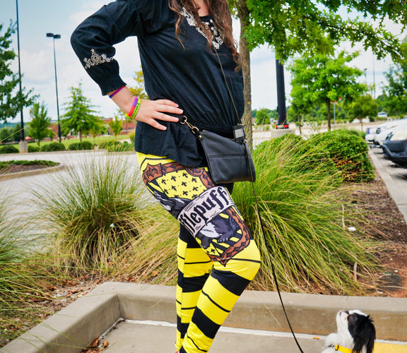 Veronica holding her right leg out, this leg of the leggings has the Hufflepuff crest on it! Hestia is watching Veronica closely!