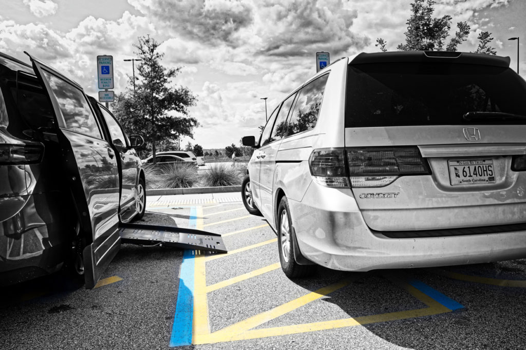 Picture is mostly in black and white with just the disabled hash marked space in color.  A van is pulled up to about half of the hash marked space, and the ramp from our van is open, showing how there is no room for a wheelchair to get into our van.