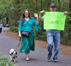 "Hestia wearing an orange and black dress, Veronica wearing a turquoise outfit and waving to the camera, and CJ wearing jeans and holding a sign that reads ""NAMI is kindness"". This was take during the walk!"