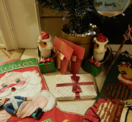 Closeup of two ceramic guinea pigs with Santa hats on, with their front feet on presents.