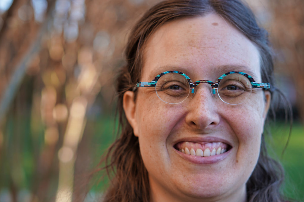 Closeup of Veronica smiling, with her face on the right and the trees on the left.