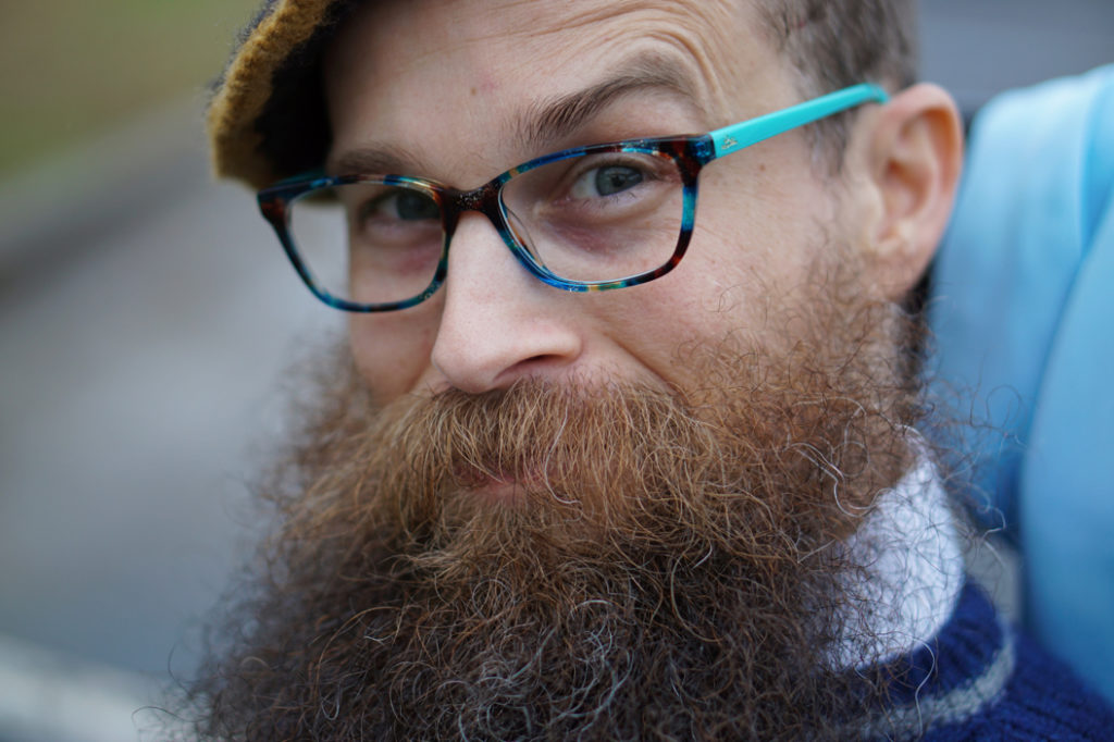 A closeup picture of a man with a bushy brown/blond beard, and turquoise tortoiseshell glasses raising one eyebrow at the camera.