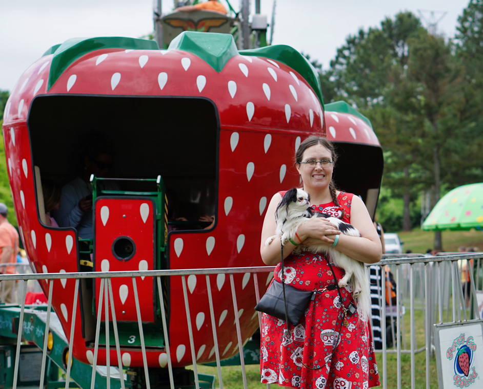 Veronica and Hestia in front of the strawberry ride, with another view showing the inside of the strawberry has people in it, spinning around.