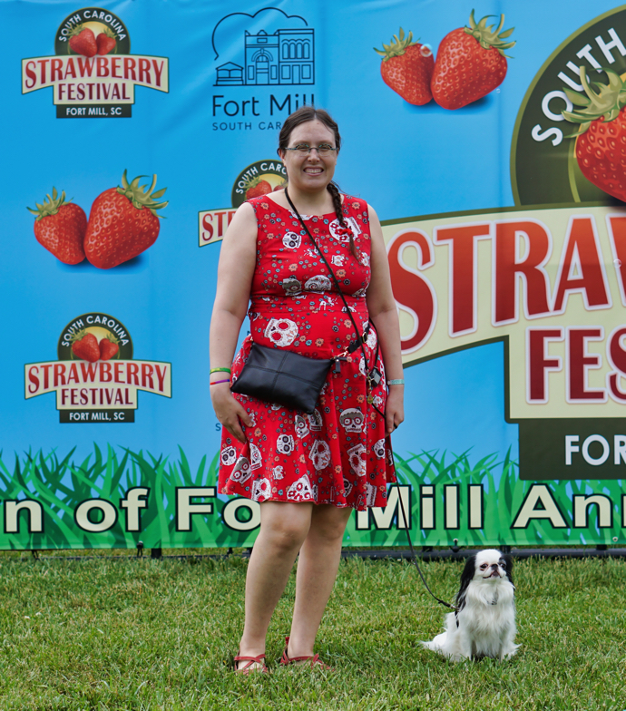 Veronica and Hestia in front of a blue backgrounded strawberry festival banner