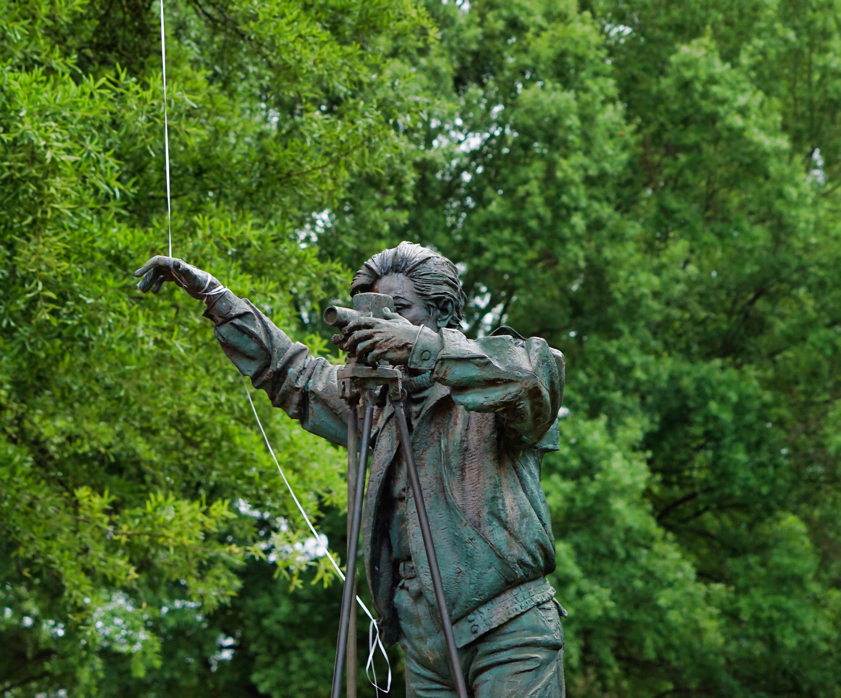 A bronze statue of a surveyor, with a slight patina, and with a real balloon string tied to his upright hand.