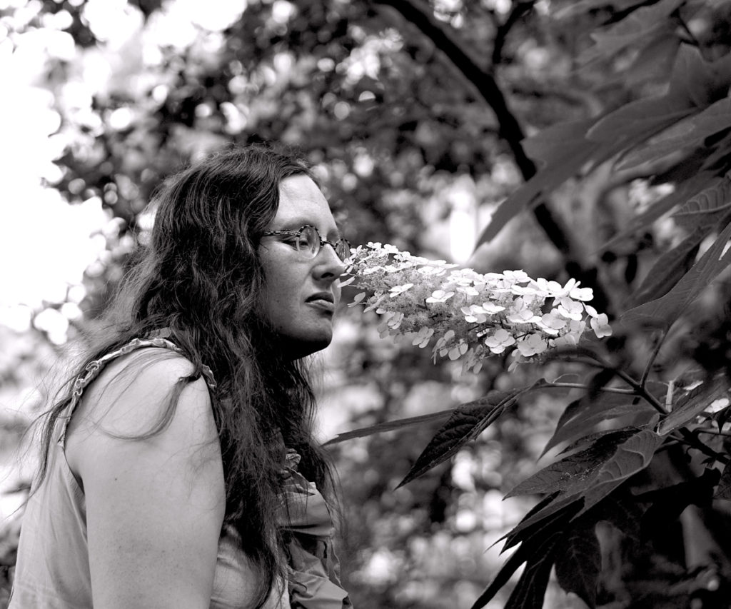 Black and white photo of Veronica sniffing a stalk of flowers