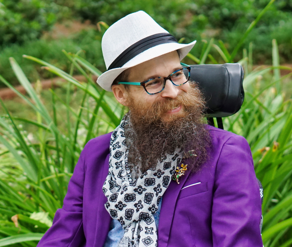 Brad wears a purple blazer, white hat, and blue and white scarf while looking to the side and smiling.