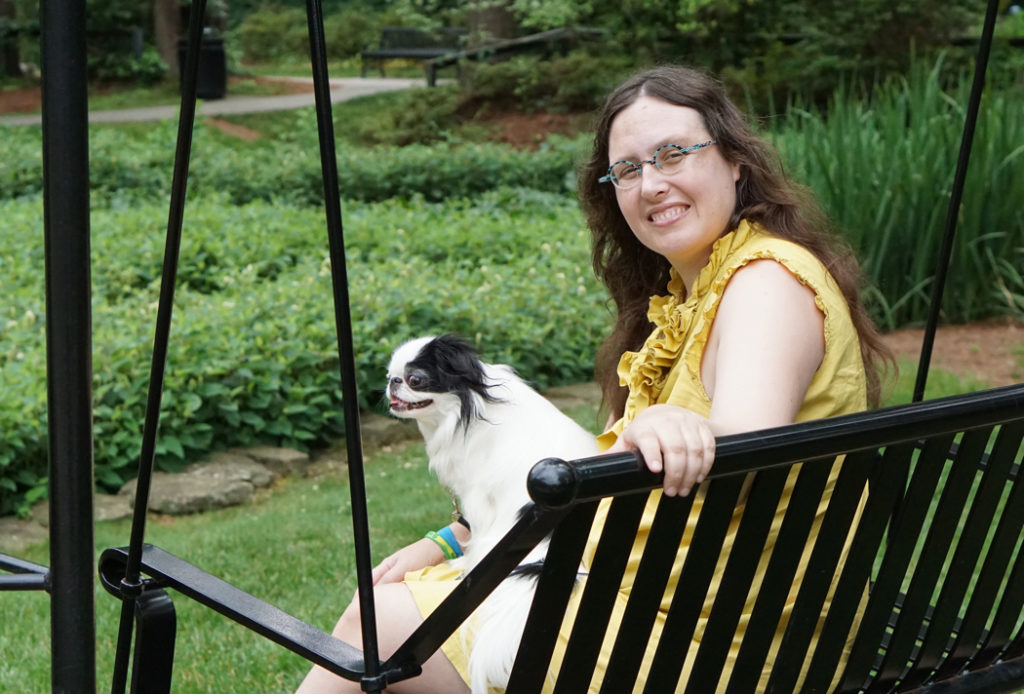 Veronica sits with Hestia on her lap on a swinging bench.  Veronica looks over her shoulder into the camera.