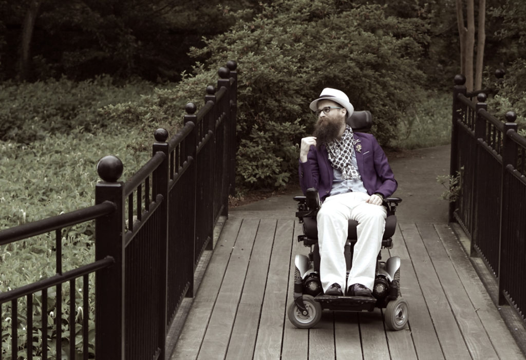 A purple sepia tinted photo of Brad stroking his beard while on the bridge.