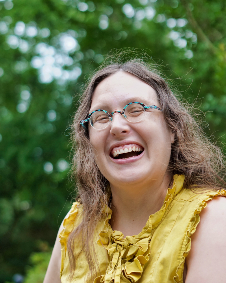 Closeup of Veronica laughing, showing her turquoise small round glasses.