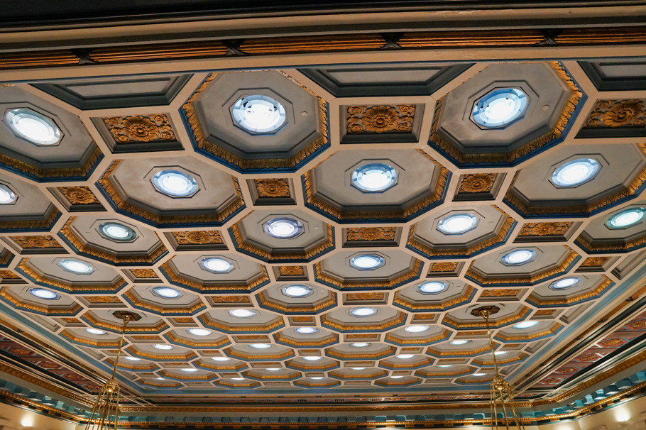 The ceiling looks like an ornate beehive with lights in the center of each cell.