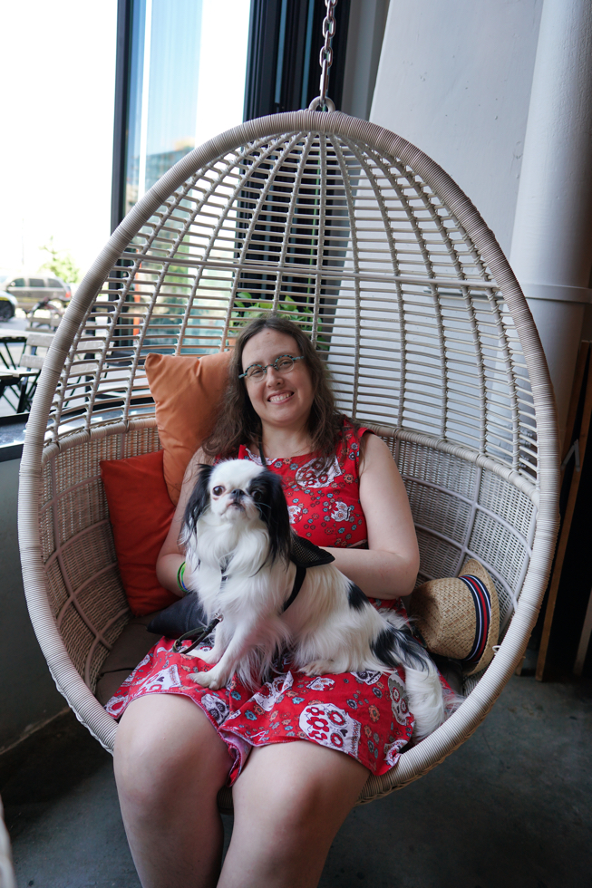 Veronica and Hestia relaxing in a hanging wicker chair at a restaurant.