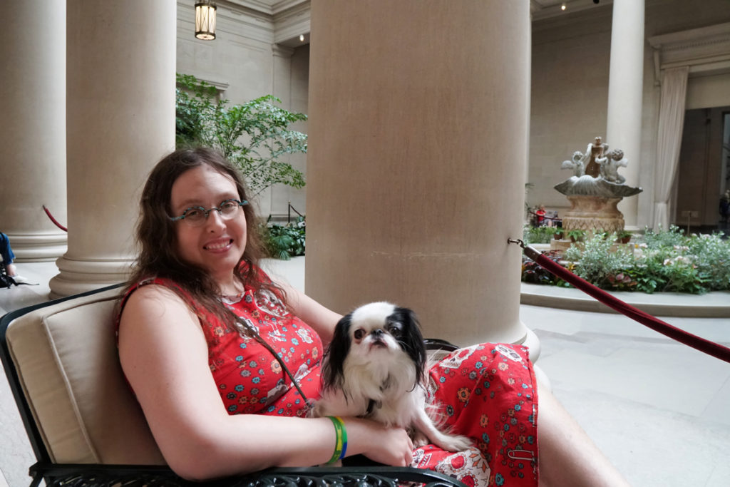 Veronica with Hestia on her lap in the art museum, hanging out in an indoor garden with lots of plants and a fountain in the background.