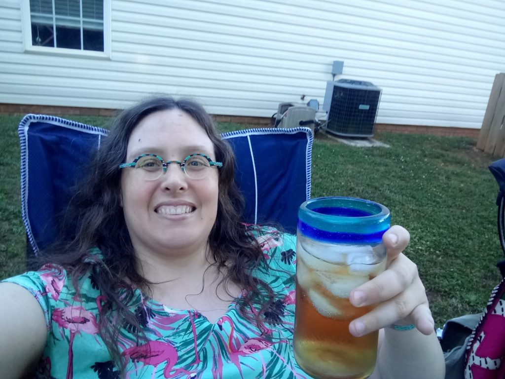 Selfie of Veronica with her iced tea, sitting in her camp chair.