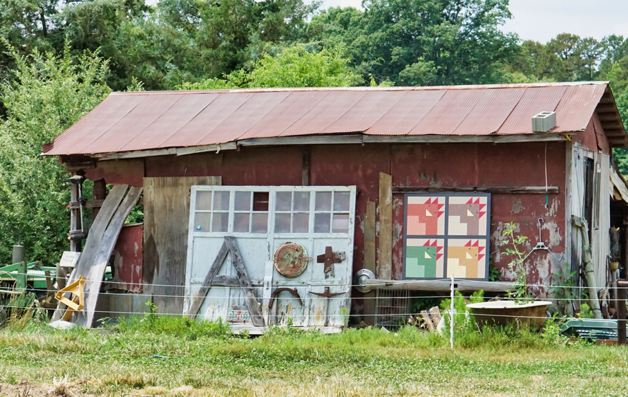 A run down barn surrounded by folk art.