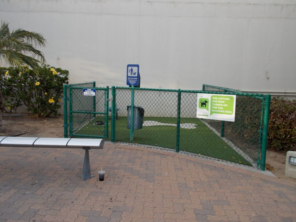 An outdoor SARA at LAX.  A small area is wire-fenced, with fake grass and a bone shaped concrete pad—but that surface is well inside the fake grass, so it's not in a great location for wheelchair accessibility.  There is a poop bag dispenser and trash can inside the SARA.