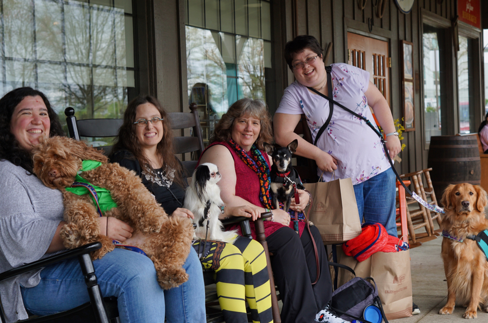 Hannah with Sasha, Veronica with Hestia, and Deanna (a woman wearing a red shirt and paw print scarf) with Maxwell Smart (a Miniature Pinscher) sit in rocking chairs outside Cracker Barrel.  Allison, a short haired woman in a purple shirt, stands next to them with her golden retriever Ruby sitting next to her.