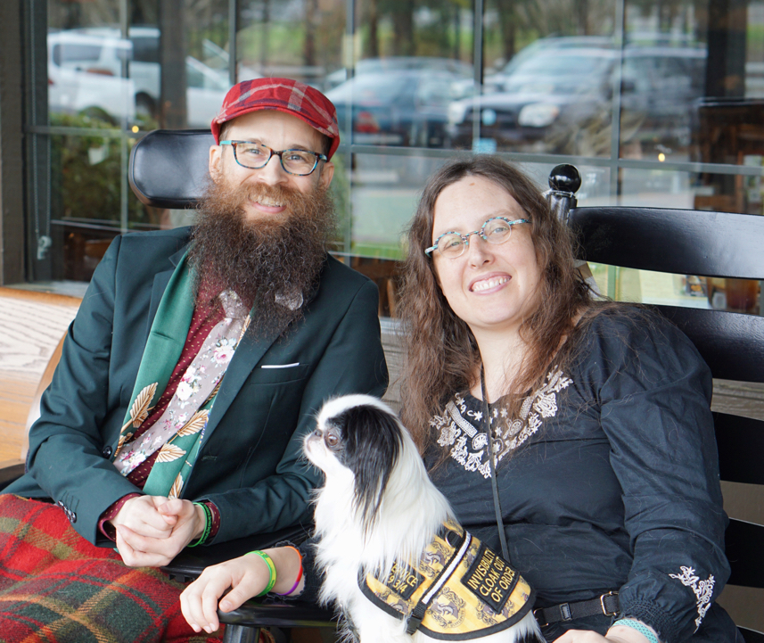 Brad, a bearded man in a wheelchair with a red plaid hat and a green jacket sits next to Veronica with Hestia outside of Cracker Barrel.