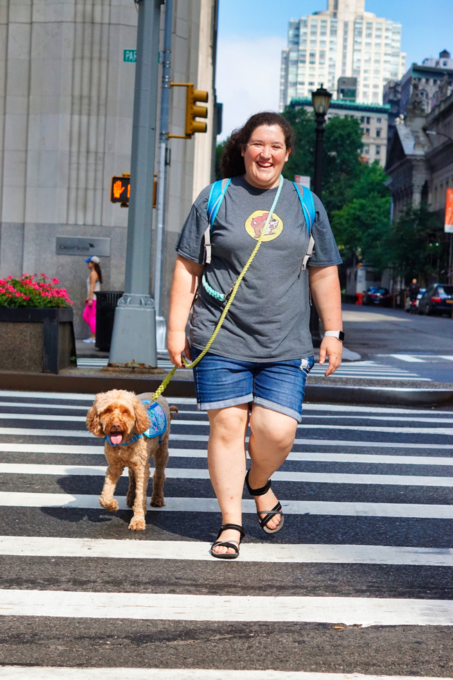 Hannah, a woman with dark curly hair and a grey shirt, walks across the street accompanied by her Labradoodle Sasha, who wears a turquoise service dog vest.