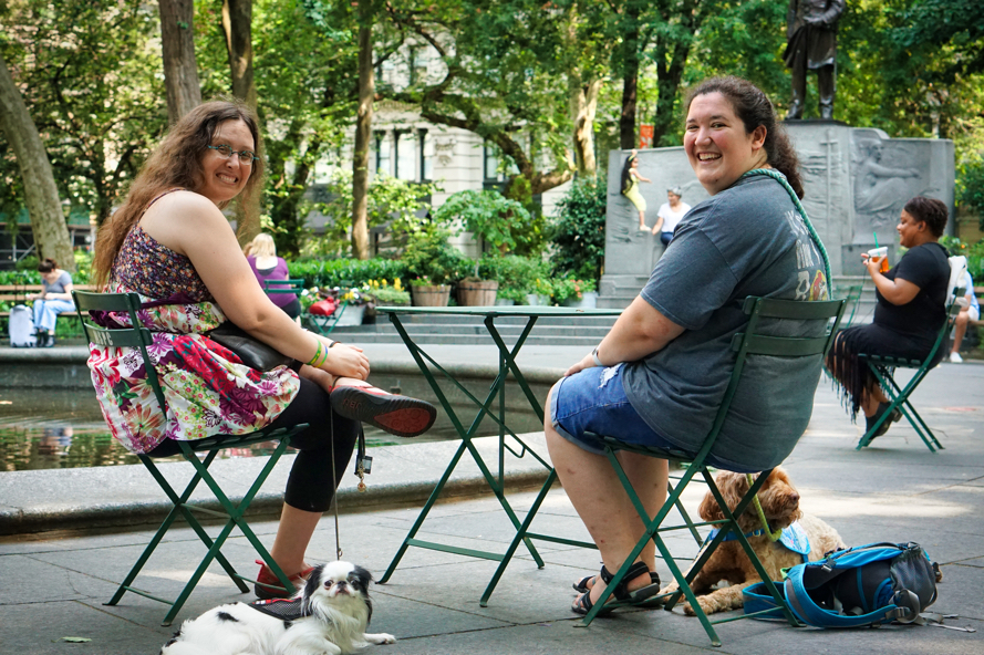 Veronica, Hannah, and Hestia smile at the camera from their table in Madison Square Park.  Sasha looks off camera to the right.