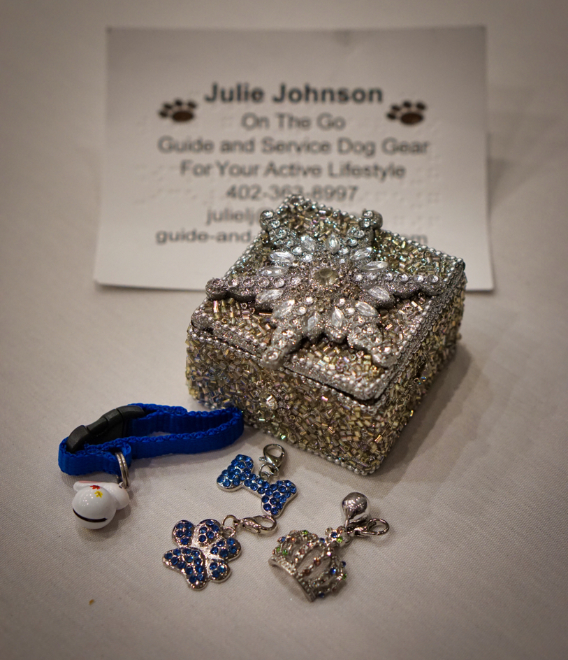 Hestia's door prize!  A silver glitter and rhinestone covered box containing four collar charms.  One is a blue attachment part with a white rabbit bell.  One has a blue rhinestone bone.  Another is a blue rhinestone paw.  Hestia's favorite is a silver crown with pastel colored rhinestones and a bell.