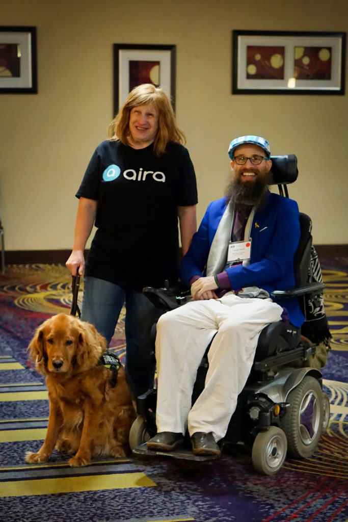 Jenine and Roger stand next to Brad.  Brad is a bearded man in a wheelchair wearing a blue blazer, white pants, and a blue plaid hat.