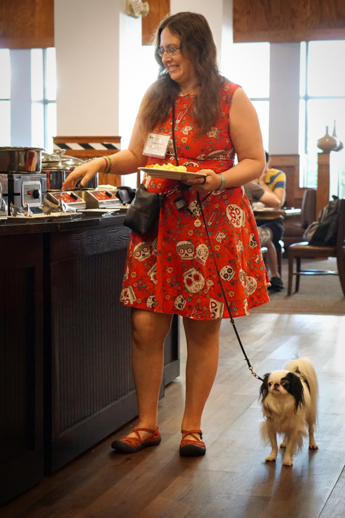 Veronica is wearing a red 50s style dress with white sugar skulls on it, and she has long brown curly hair.  She is filling her breakfast plate with food as Hestia, a small black and white dog with a smushed face, stands on the floor next to her looking bored.