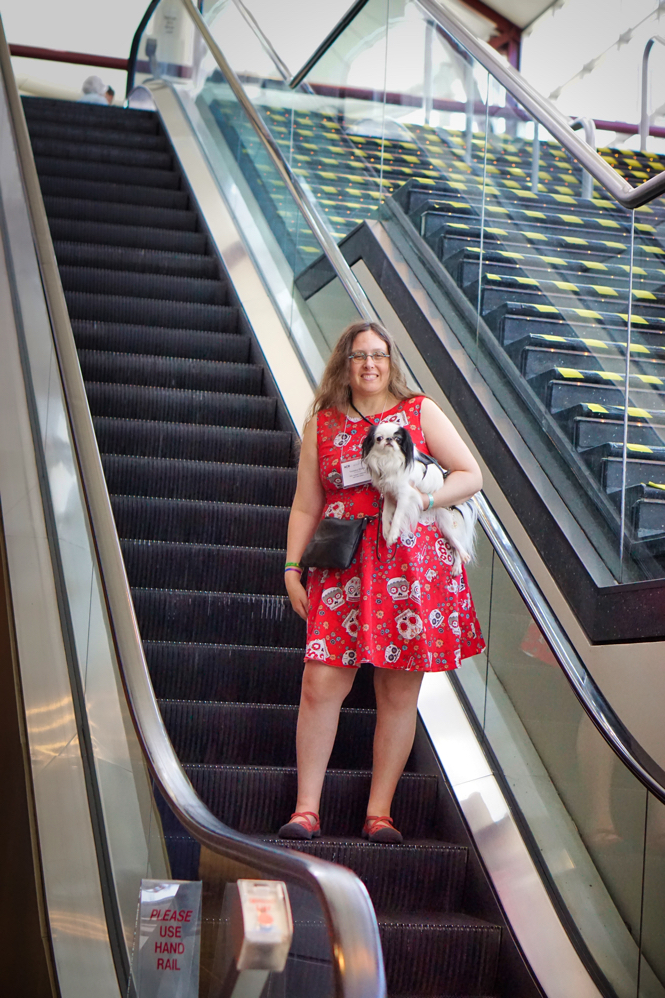 Veronica holds Hestia and smiles as she descends the escalator in the convention center.  The stairs next to the escalator have been marked with yellow and black high visibility tape.