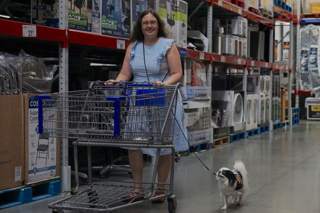 Veronica looks up and smiles at the camera as she pushes the cart, while Hestia walks along beside Veronica.