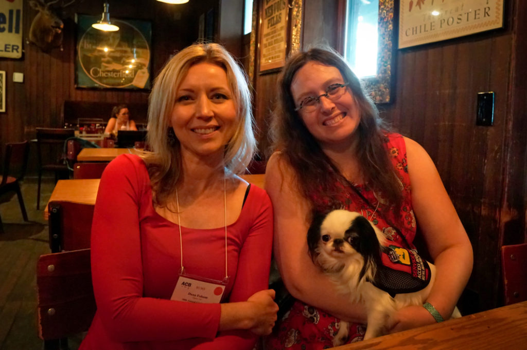 Dana is a blond woman in a red dress.  She sits next to Veronica, who has Hestia on her lap, in the BBQ restaurant.