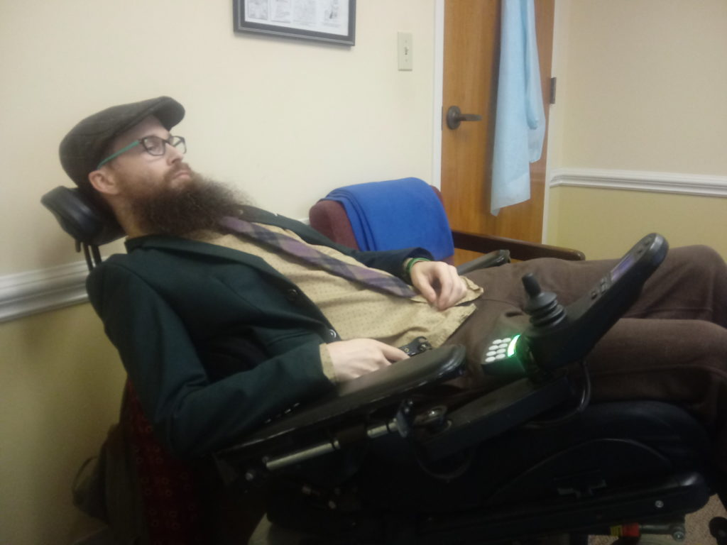 A bearded man reclines in a power wheelchair, and looks extremely tired.  He has on brown pants, a tan shirt, a green blazer, a purple plaid tie, and a brown newsboy cap.