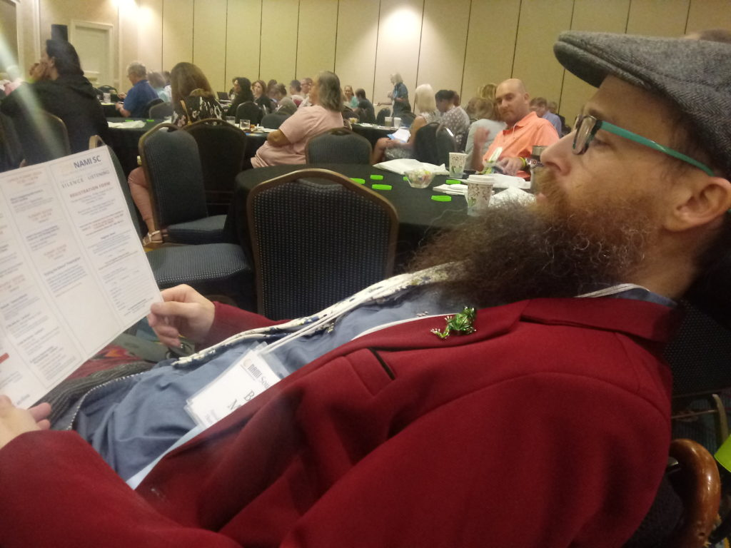 Brad wearing a red blazer and a newsboy hat reclines and looks at the program for the day.