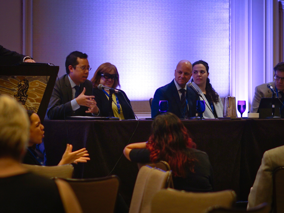 A closeup of a panel of presenters, one of whom is Jenine!  She is the one with the reddish hair wearing Aira sunglasses.
