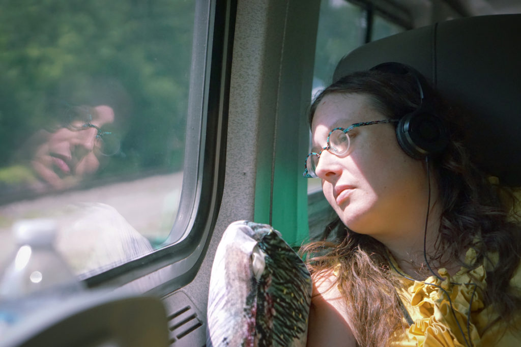 Veronica wears her ruffled yellow dress and headphones, as she looks wistfully out the window of the train on the way home.