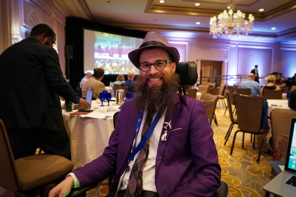 Brad is looking stylish in his purple jacket and hat.  He has both an airplane brooch and a white greyhound brooch on his lapel in honor of our talk about service dogs in airports.