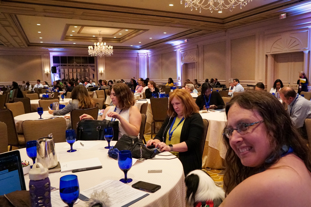 Veronica smiles at the camera, while Jenine sits next to her and focuses on her phone before we present.  The room is full of people!